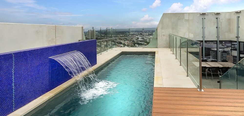 Local Pools and Spas Sydney Fastlane lap pool built above the ground with a water feature